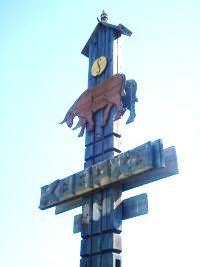 Бык с приветствием, сделанный из дерева на въезде в Куорку